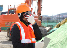 Construction worker with building plans and cellphone Stock Image