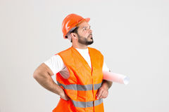 Construction Worker with Building Plans. Young Construction Worker in Safety Helmet and Orange Jerkin is Holding a Building Plans  Isolated on White Background Royalty Free Stock Photos