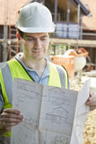 Construction Worker On Building Site Looking At House Plans. Male Construction Worker On Building Site Looking At House Plans royalty free stock image