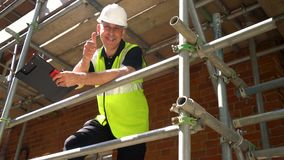Construction worker on building site standing on scaffolding thumbs up to camera stock video
