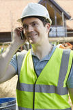 Construction Worker On Building Site Using Mobile Phone Stock Photography