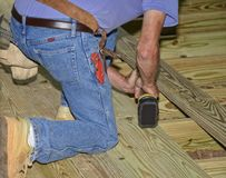 Construction Worker Building a Wood Deck. Man on his knees drilling the boards of a new deck area royalty free stock photography