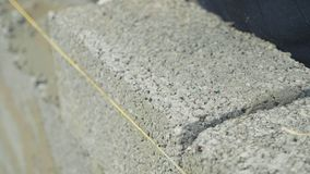 Construction worker builds brick wall, closeup view at construction site. Slow motion stock footage