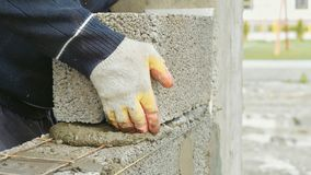 Construction worker builds brick wall, closeup view at construction site stock image