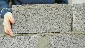 Construction worker builds brick wall, closeup view at construction site stock photography
