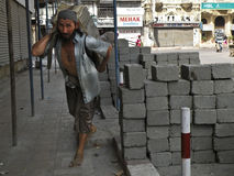 Construction worker carrying concrete block Stock Photos