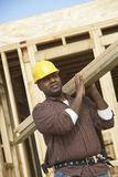 Construction Worker Carrying Lumber Royalty Free Stock Photos