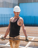 Construction worker carrying steel bars. Authentic construction worker carrying reinforcement steel bars in construction site Stock Photos