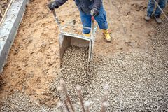 Construction worker carrying and unloading gravel and stones with wheelbarrow for foundation of building Royalty Free Stock Photo