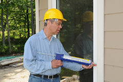 Construction worker with a caulking. Construction worker sealing window frames with a caulking gun Stock Photo