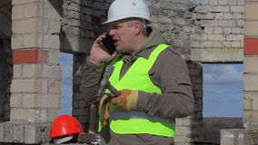 Construction worker with cell phone, trowel and mallet stock footage