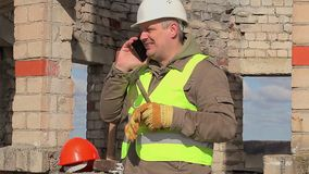 Construction worker with cell phone, trowel and mallet stock video