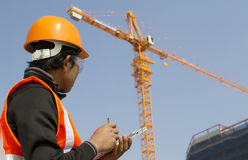 Construction worker with crane in background Royalty Free Stock Image