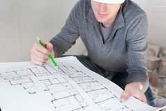 A construction worker checking documents with pencil in his hand Stock Image