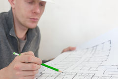 A construction worker checking documents with pencil in his hand Royalty Free Stock Photography