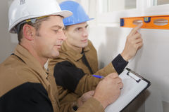 Construction worker checks level while supervison writes it down Royalty Free Stock Photography