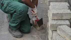 Construction worker cleaning bricks stock video