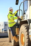 Construction worker climbing a wheel loader Stock Images