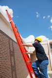 Construction Worker Climbs to Roof Royalty Free Stock Images