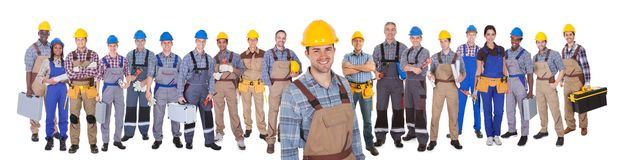 Construction worker with colleagues over white background Royalty Free Stock Photos