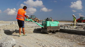 Construction worker compacting soil on a runway construction site stock footage