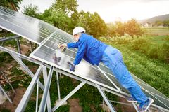 Installing of solar photo voltaic panel system. Construction worker connects photo voltaic panel to solar system using screwdriver. Professional installing and Stock Images