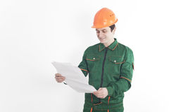 Construction worker is considering the construction plan. Construction worker in green uniform and a orange helmet is considering the construction plan. White Stock Images