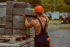 Construction worker. Construction worker carry bricks. Construction worker unload truck. Construction worker in working. Uniform. Building tomorrow world today royalty free stock image