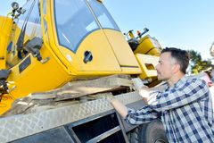 Construction worker controls lifting crane in truck. Construction worker controls of lifting crane in truck Royalty Free Stock Images