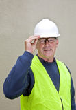 Construction worker in correct safety clothing. Building worker with safety gear including hard hat, safety glasses and fluorescent jacket Stock Photo
