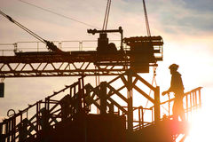 Construction worker, crane and building at sunset Royalty Free Stock Images