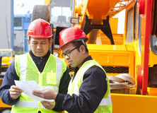 Construction worker and crane truck. Construction workers discussing new project building royalty free stock images