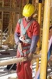 Construction Worker Cuts Board - Vertical Stock Photo