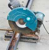 Construction worker cuts rebar circular saw Royalty Free Stock Images