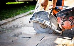 Construction worker cutting Asphalt paving for sidewalk Stock Photo