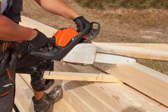 Construction Worker Cutting Beam with saw. Workers cutting timber wood with chainsaw. Saw sawing timber. Stock Photos