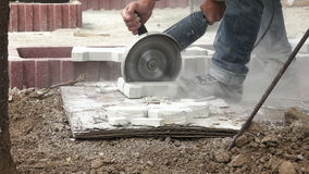 Construction worker cutting pavement stone with an angle grinder 4K with audio. Construction worker cutting pavement stone with a heavy duty angle grinder 4K stock footage