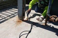 Construction worker cutting steel column by welder machine.  Royalty Free Stock Photo