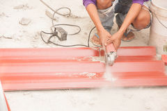Construction worker is cutting tile roof Stock Photography