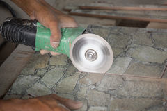 Construction worker cutting a tile using an angle grinder Stock Images