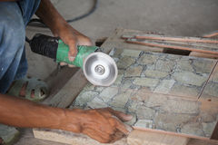Construction worker cutting a tile using an angle grinder Royalty Free Stock Photography