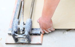Construction worker is cutting tiles at home, renovation Royalty Free Stock Image