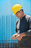 Construction worker cutting wire with pliers. Authentic construction worker cutting reinforcement binding wire with a pair of pliers Stock Photography