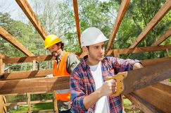 Construction Worker Cutting Wood With Handsaw At Stock Photography