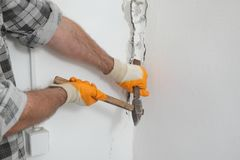 Construction site, old building demolishing. Construction worker demolishing hole at brick wall with chisel tool and hammer Royalty Free Stock Image