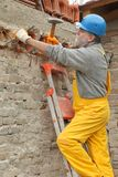 Construction site, old building demolishing. Construction worker demolishing old brick wall with chisel tool and hammer Stock Images