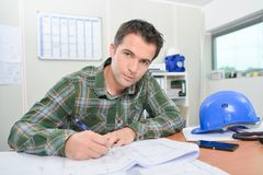 Construction worker at desk royalty free stock photography