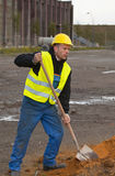 Construction worker digging ground. Construction worker in workwear and in yellow hardhat digging sand with shovel Royalty Free Stock Photo