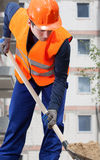 Construction worker digging sand with shovel Stock Photo