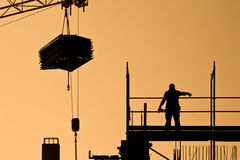 Construction worker directing crane with load. Silhouette of construction worker on a frame directing a crane with heavy load Royalty Free Stock Photos